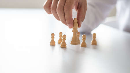 Closeup of businessman hand holding king chess figure with pawn figures around him in a conceptual image of teamwork and leadership.