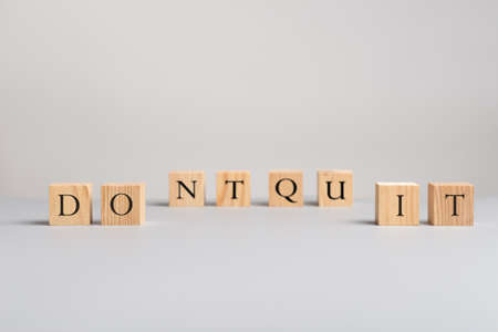 Wooden blocks with letters spelling dont quit or do it sign over grey background in a motivational image.
