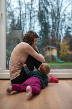 Young mother sitting worried or depressed by the window in a living room with her baby daughter lying on the floor reaching out to her.