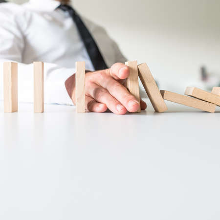 Businessman placing his hand to stop falling dominos and prevent the crisis in a conceptual image.