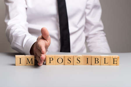 Wooden blocks spelling the word impossible with businessman pushing away letters im with his hand.
