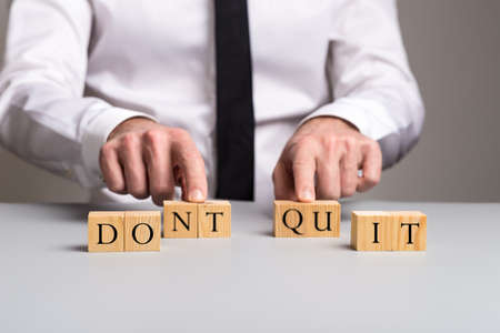 Businessman making a dont quit sign of wooden blocks with letters in a conceptual image.