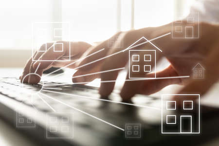 Online real estate concept - male hands typing on computer keyboard with house shaped icons over the image.