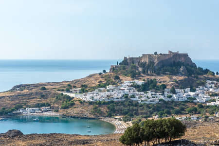 View of an ancient Greek acropolis of Lindos above the bay of a beautiful blue ocean.