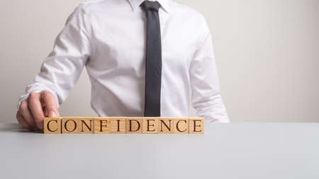 Businessman sitting at office desk with wooden cubes spelling Confidence in front of him.