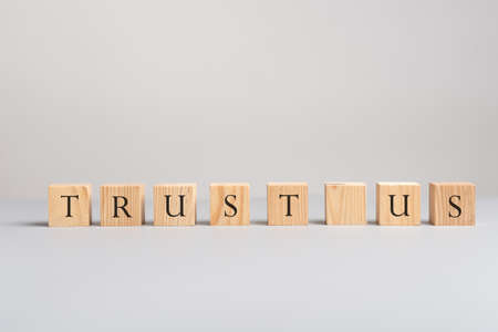 Wooden blocks placed in a row spelling trust us in a conceptual image of business support and customer service.