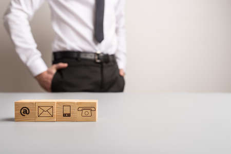 Communication symbols on wooden blocks with businessman standing in background and copy space on the right side of an image. Imagens