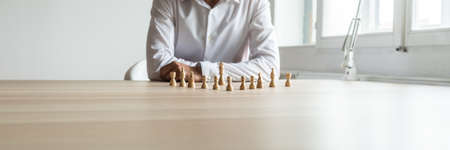 Wide view image of business executive sitting at his desk with chess pieces positioned in front of him in a conceptual image