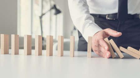 Bedrijfscrisisbeheerconcept - bedrijfsbemiddelaar die vallende dominostenen met zijn hand stopt.