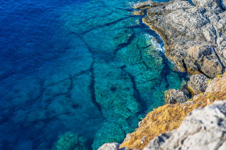 Top view of beautiful blue sea with rock bottom and cliff rising from it. Stockfoto