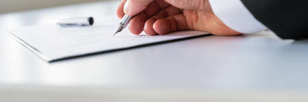 Closeup of businessman signing contract with ink pen.