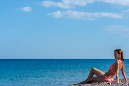 Pretty young woman in pink bikini sitting on a pebble beach by beautiful blue ocean looking into the distance.
