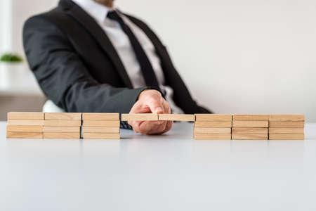 Geschäftsmann, der an seinem Schreibtisch sitzt und eine Brücke aus Holzpflöcken in einem konzeptionellen Bild der Unternehmensfusion macht.