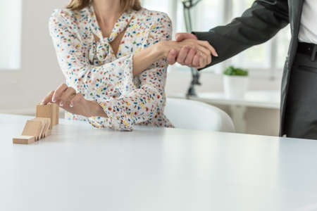 Businesswoman stopping falling dominos with her finger and shaking her partners hand at the same time in a crisis management concept image.