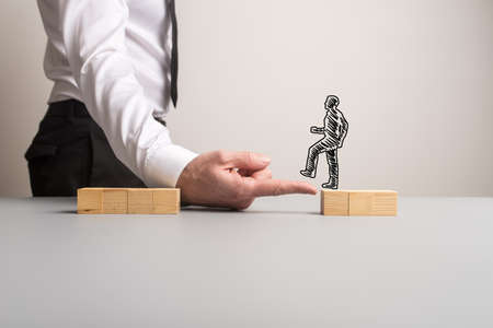 Businessman making a bridge of his finger for a silhouetted businessman to walk across one pile of wooden blocks to the other in a conceptual image. With copy space. Stock Photo