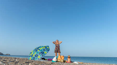 Young mother on a beautiful pebble beach in Greece with her toddler daughter.