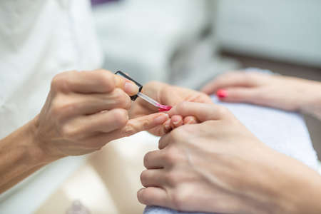 Closeup of manicurist applying shiny red nail polish to a womans nail in a cosmetic salon.