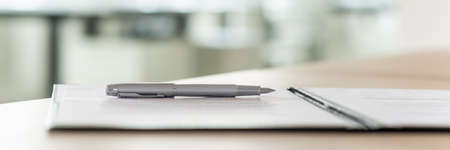 Wide view image of an ink pen lying on a contract in an open folder. Stockfoto