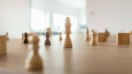 Chess figure king in the middle of an office desk wit other figures around it in a conceptual image of business leadership and power.