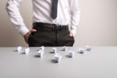 Businessman standing behind a desk with origami paper made boats placed in an arrow shaped position in a conceptual image.