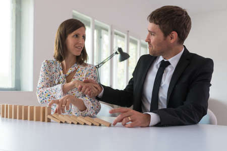 Businesswoman stopping falling dominos with her finger and shaking hands with her business partner in a conceptual image.
