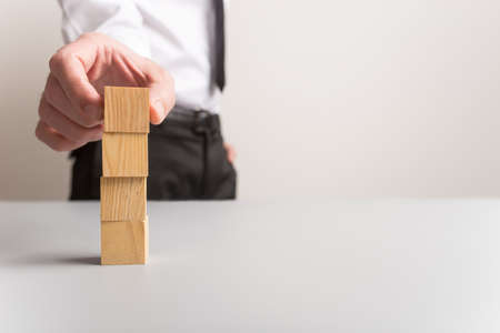 Businessman stacking four blank wooden cubes with plenty of copy space. Standard-Bild