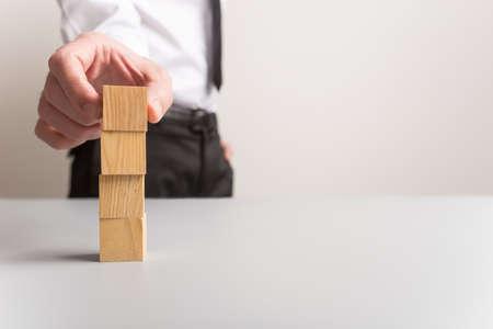 Empresario apilando cuatro cubos de madera en blanco con mucho espacio de copia.