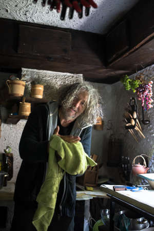Senior man holding kitchen cloth in an rustic old kitchen.