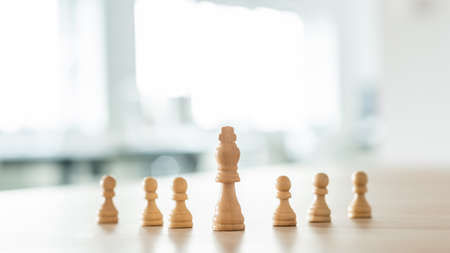 Chess pieces of king and pawns placed on an office desk in a conceptual image. Foto de archivo