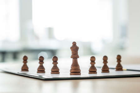 Chess pieces of king and six pawns placed on a business document in a conceptual image.