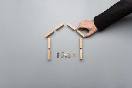 Hand of insurance agent making house of wooden pegs to shelter a family made of pebbles. With copy space.