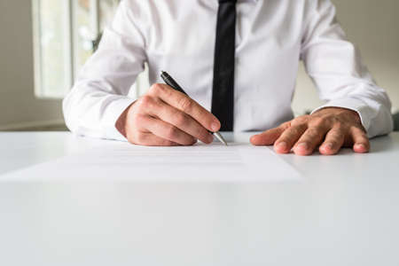 Front view of businessman at his office desk signing a document, contract or application form.