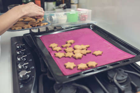 Woman taking freshly baked home made cookies off the hot tray in a home kitchen. Stock Photo