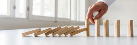 Hand van een bedrijfscrisismanager die vallende dominostenen stopt om een totale ineenstorting te voorkomen en stabiliteit te bewerkstelligen. Stockfoto