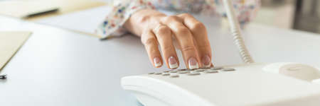 Wide view image of a secretary with perfect french manicure dialing telephone number using white landline phone. Stock Photo