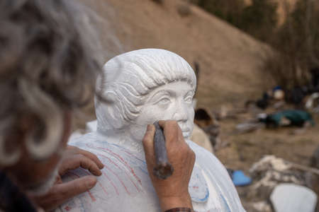 Sculptor working on his statue using a chisel to work on details. Archivio Fotografico