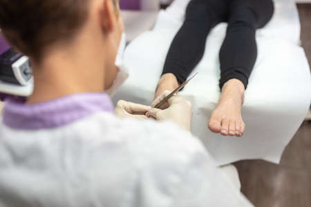 Over the shoulder view of podiatrist removing cuticle from toenails in a pedicure treatment.