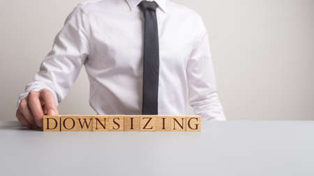 Business executive sitting at his office desk with the sign downsizing in front of him in a conceptual image. Stock Photo
