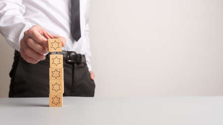 Businessman stacking five wooden cubes with stars on them in a conceptual image of quality and guarantee. With copy space.