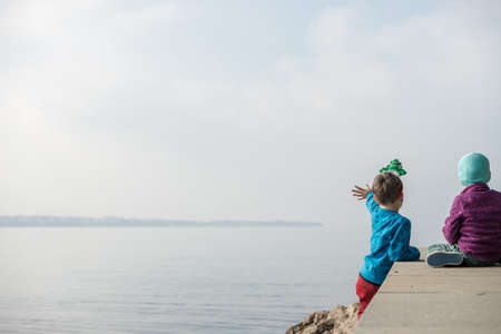 Two toddler boys sitting on a pier looking and waiving into the distance on an autumn day.