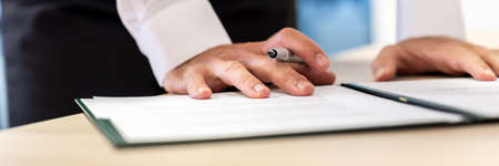 Wide view image of businessman holding ink pen leaning on a document in a folder proofreading before signing it.