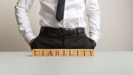 Businessman standing behind an office desk with a Liability sign on it in a conceptual image of obligation and responsibility. Stock Photo