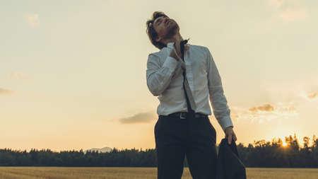 Uitgeputte zakenman die in de natuur onder een avondlucht staat en zijn das losmaakt van de stress.
