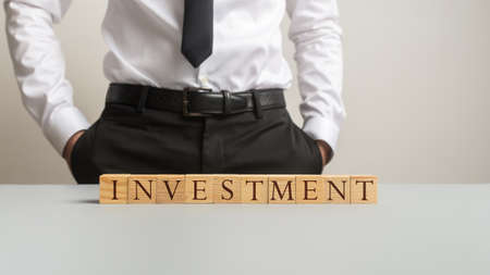 Financial business adviser standing behind a desk with an Investment sign made of wooden blocks on it.