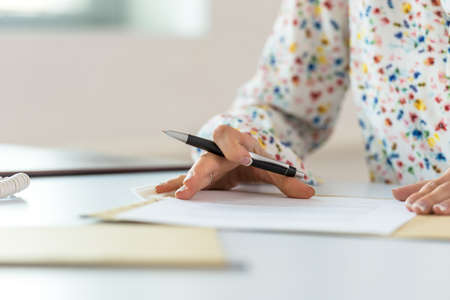 Low angle view of businesswoman at her office desk proofreading a document or contract in a paper folder before signing it.