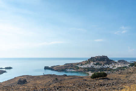 Landscape view of beautiful bay of Lindos with ancient acropolis on top of a hill. 免版税图像