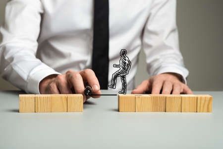 Business executive drawing a line between two separated piles of wooden blocks for a silhouetted businessman to walk across in a conceptual image.