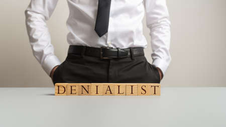 Man in a suit standing behind an office desk with a word Denialist spelled with wooden cubes in a conceptual image. Stockfoto