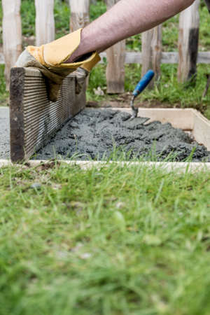 Low angle view of a man wearing protective work gloves leveling fresh cement as he makes a foundation in backyard.