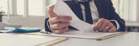 Imagen de vista amplia del asesor financiero sentado en su escritorio mirando el recibo mientras realiza un informe de balance anual. Foto de archivo